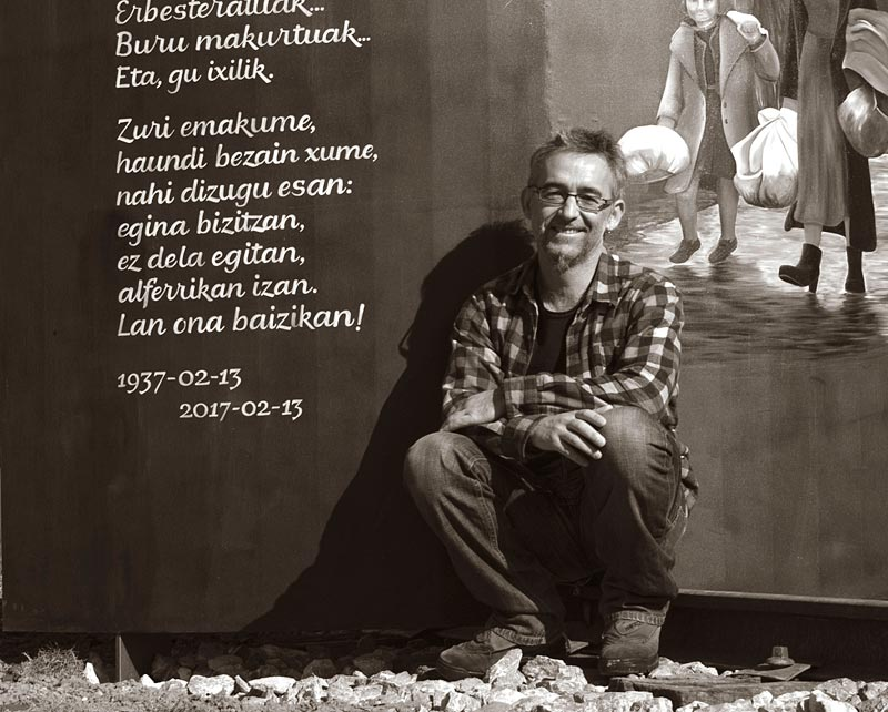 Brush lettering on the refugee monument and the author (Juan Luis Blanco)